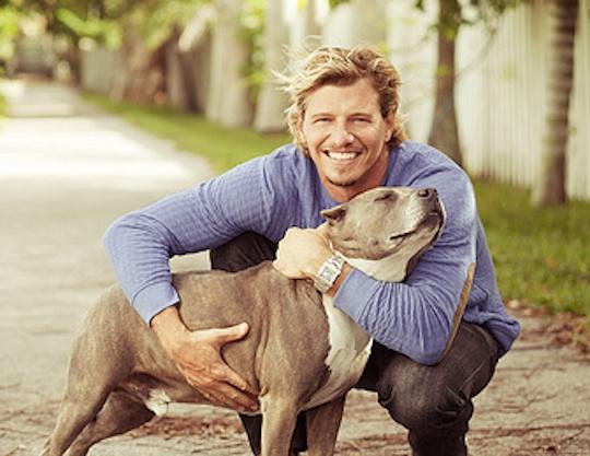Man hugging his pet dog (American Pit Bull Terrier)